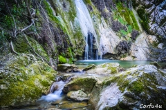 The water fall from a height greater than 10m into the verdant ravine.